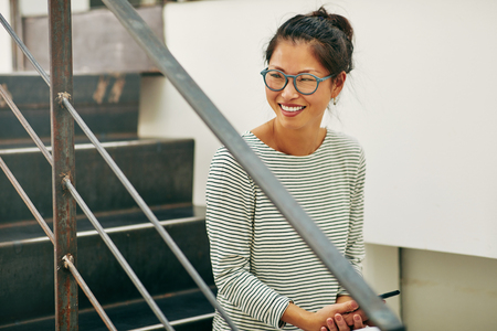 Young Asian businesswoman wearing glasses and smiling while sitting on stairs in an office reading a funny text message on her cellphone Stock fotó