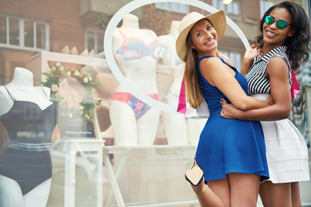 Two happy elegant young women out shopping for couture fashion standing outside a store window flirting with the camera with mischievous smiles