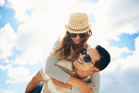 Handsome young man with his loving wife or girlfriend having fun relaxing on summer vacation piggy back riding against a sunny cloudy blue sky Banco de Imagens