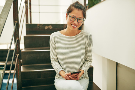 Young Asian businesswoman wearing glasses and smiling while sitting on stairs in a office sending a text message on her cellphone Stockfoto