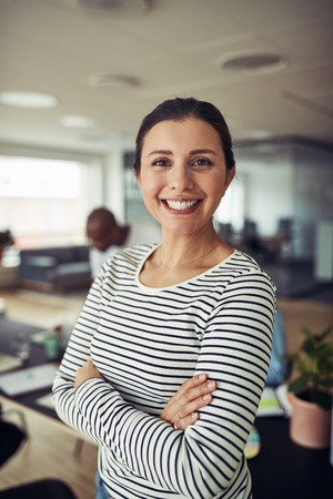 Smiling young businesswoman standing confidently with her arms crossed in an office with colleagues sitting at a table in the background