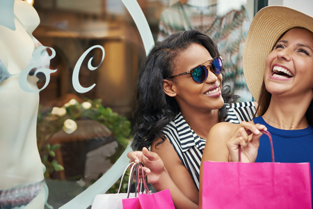 Close up of smiling African woman with laughing Caucasian friend while holding shopping bags outside near retail store window Stock Photo