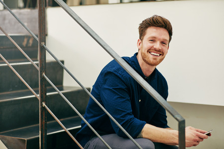 Smiling young businessman sitting on stairs in an office reading text messages on a cellphone