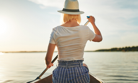 Rearview of a young woman looking at the view while paddling a canoe on a scenic lake on a late afternoon in summer