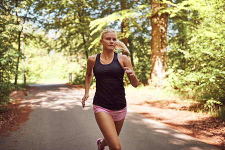 Fit young blonde woman in shorts and a tanktop jogging alone on a path through a forest on a sunny day