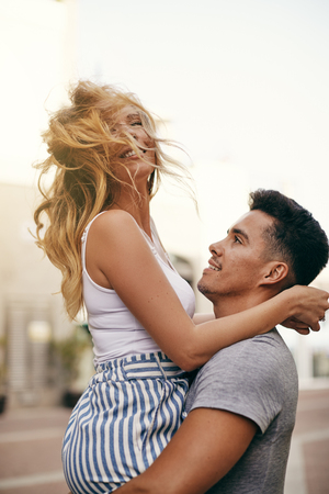 Laughing young woman being held in the air by her smiling boyfriend while having a good time together in the city