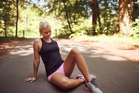 Fit young blonde woman in sportswear sitting alone on a forest path taking a break from a run