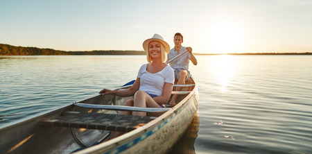 Smiling young woman sitting with her boyfriend in a canoe on a still lake on a late summer afternoon