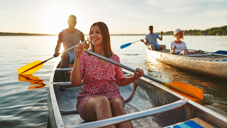 Smiling young woman paddling a canoe with her boyfriend and friends on a lake on a late summer afternoon Stock Photo