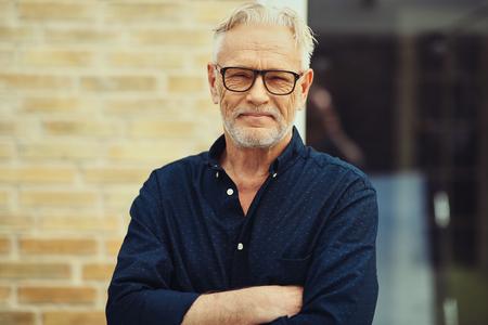 Hombre mayor sonriente con barba y gafas de pie con los brazos cruzados afuera frente a su casa