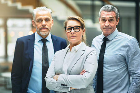 Confident mature businesswoman standing with her arms crossed with two male colleagues in the lobby of a modern office building