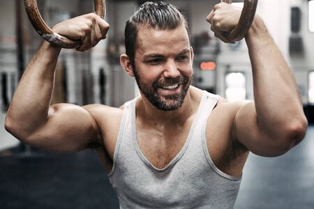 Fit young man in sportswear smiling while working up a sweat during a workout session on rings at a health club Banque d'images