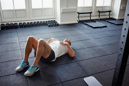 Tired senior man in sportswear lying alone on the floor of a gym after working out Stock Photo