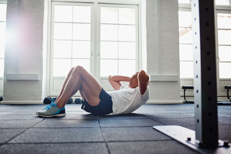Focused senior man in sportswear doing sit ups alone while working out on the floor of a gym Stock Photo