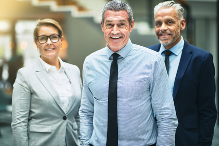 Smiling mature businessman standing with two coworkers in the lobby of a modern office building