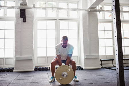 Mature man in sportswear standing alone in a gym focused on lifting weights during a workout Stock Photo