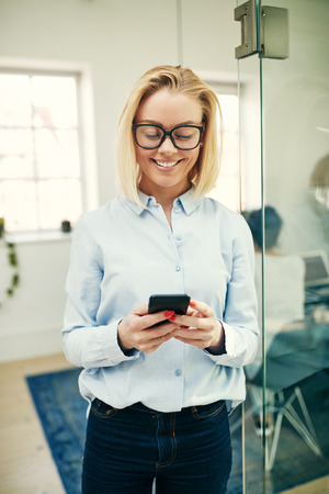 Smiling young businesswoman sending text messages on her cellphone while standing in a modern office Stock Photo