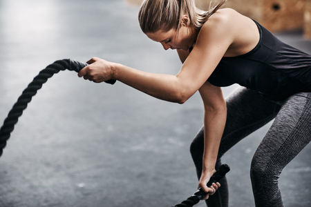 Fit young blonde woman in sportswear working out with ropes during an exercise session in a gym Archivio Fotografico - 108607357
