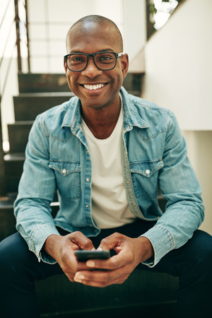 Smiling young African businessman wearing glasses and sending a text message on his cellphone while sitting on stairs in an office