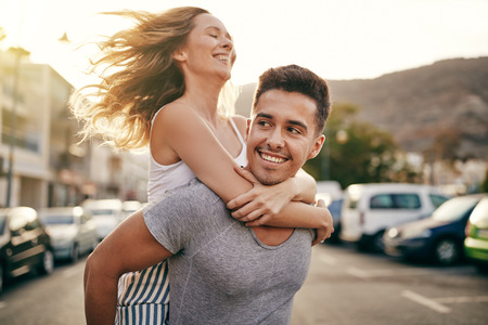 Smiling young man carrying his girlfriends on his shoulders while enjoying a day together in the city Archivio Fotografico