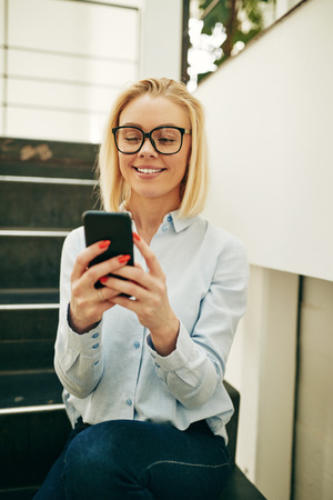 Smiling young businesswoman wearing glasses and sitting on stairs in a modern office readng text message on her cellphone