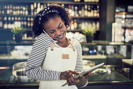 Smiling young African entrepreneur standing in her cafe taking reservations on a cellphone and using a tablet 写真素材