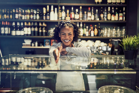Smiling young African entrepreneur standing behind the counter a trendy cafe extending her arm to shake hands Stock Photo
