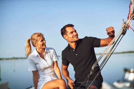 Smiling young couple enjoying an afternoon sailing together while sitting on the deck of their yacht
