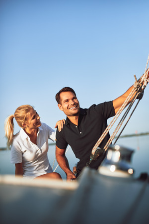 Smiling young couple sitting on the deck of their yacht enjoying an afternoon sailing together