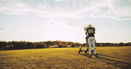 Young American football player practicing tackles and defensive drills outside on a sports field in the late afternoon
