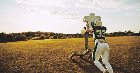 Young American football player doing tackles and defensive drills outside on a sports field in the late afternoon