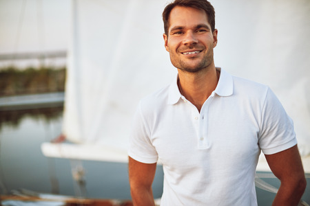 Smiling young man standing alone on the deck of his yacht enjoying a sunny day sailing
