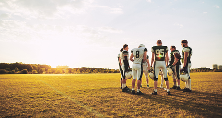 Group of young American football players standing together on a sports field in the afternoon during practice Stock Photo