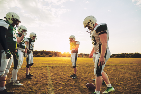 Group of young American football players lining up for a practice session on a sportsfield field in the afternoon