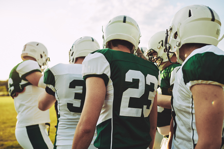 Group of young American football players standing on a sports field talking together during practice