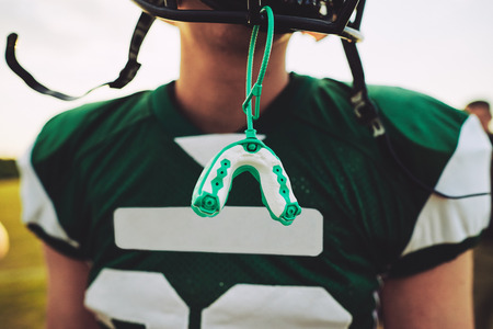 Closeup of a mouthguard hanging off the helmet of an American football player during a team practice session