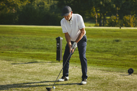 Sporty senior man teeing off with his driver while playing a round of golf on a sunny day