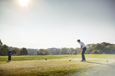 Sporty senior man about tee off with his driver while playing a round of golf on a sunny day