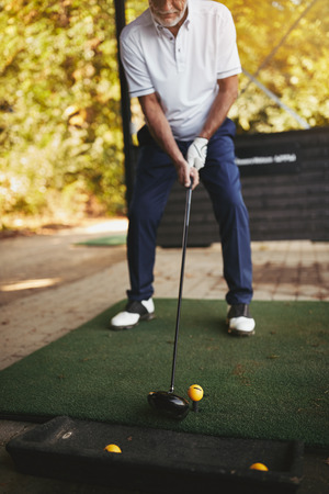 Sporty senior man standing outside practicing his golf swing at a driving range on a sunny day