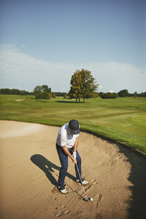 Senior man attempting to chip out of a sand trap while playing a round of golf on a sunny afternoon