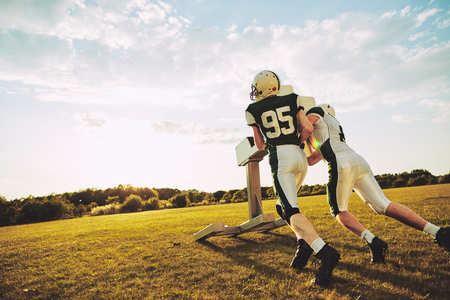 Two American football players practicing tackles with a tackle sled outside on a sports field in the late afternoon Stock Photo