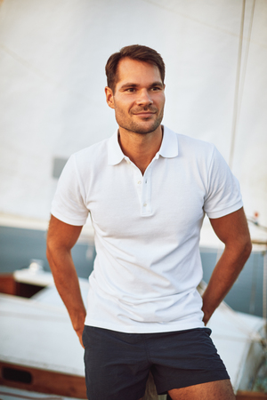 Handsome young man standing alone on the deck of his yacht enjoying a sunny day sailing