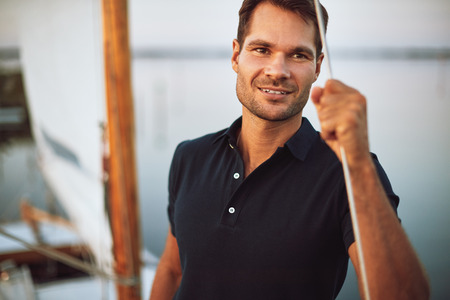 Handsome young man leaning on the rigging of his yacht and smiling while out for a sail
