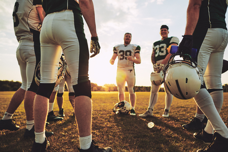 Group of young American football players standing in a circle discussing strategy during an afternoon practice