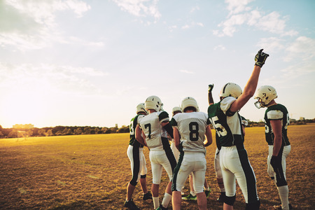 Team of young American football players cheering and celebrating together on a sports field during an afternoon game