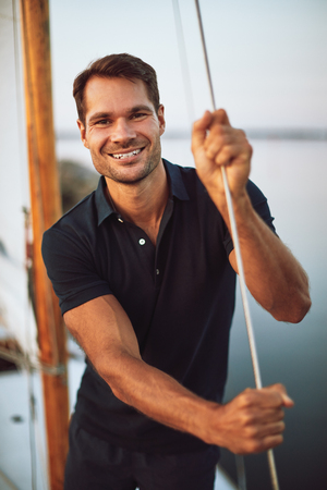 Smiling young man leaning on some rigging while standing on the deck of his yacht enjoying a sunny day sailing