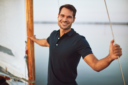 Smiling young man leaning on some rigging while standing alone on the deck of his yacht enjoying a sunny day sailing Stok Fotoğraf