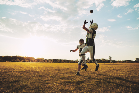 Young American football player receiving a pass during team practice on a football field in the afternoon