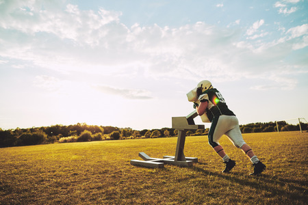 Young American football player doing defensive drills and practicing tackles with a sled on a sports field in the late afternoon