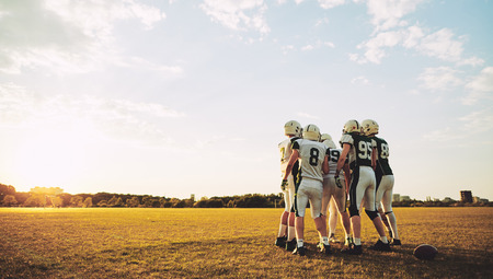 Group of young American football players standing together on a field during an afternoon practice